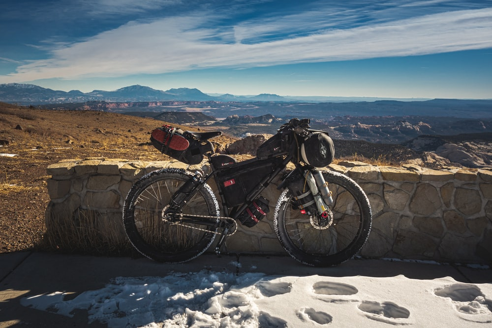 black and red mountain bike on snow covered ground during daytime