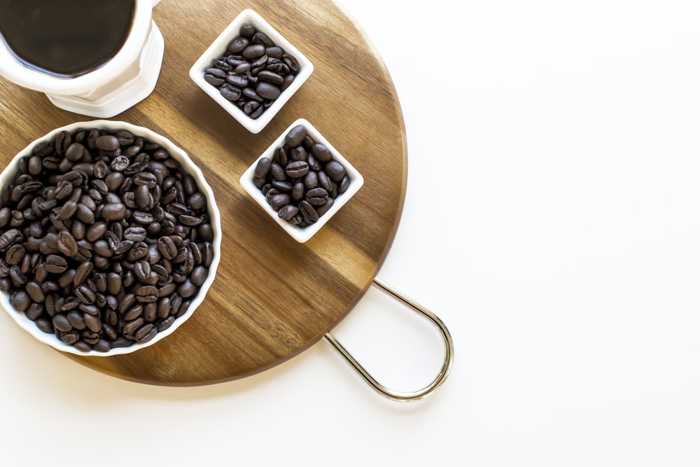 black coffee beans on brown wooden round bowl