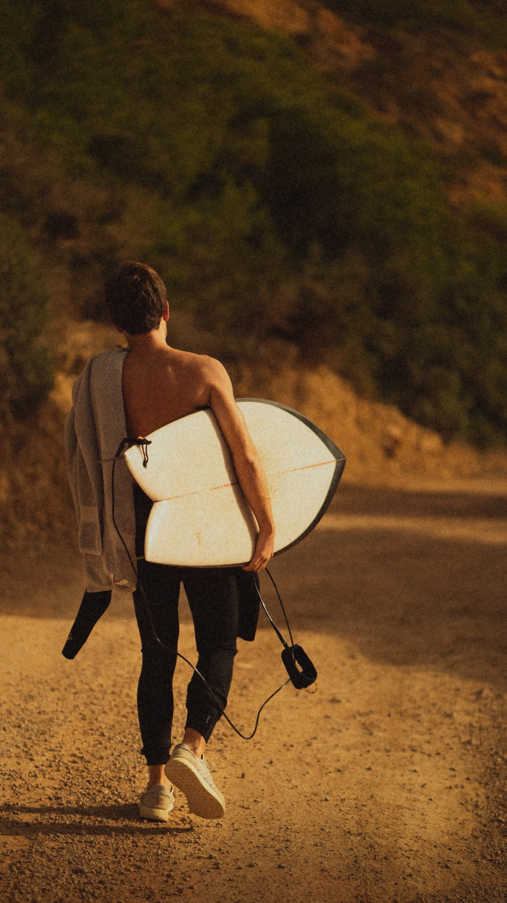 topless man holding white surfboard