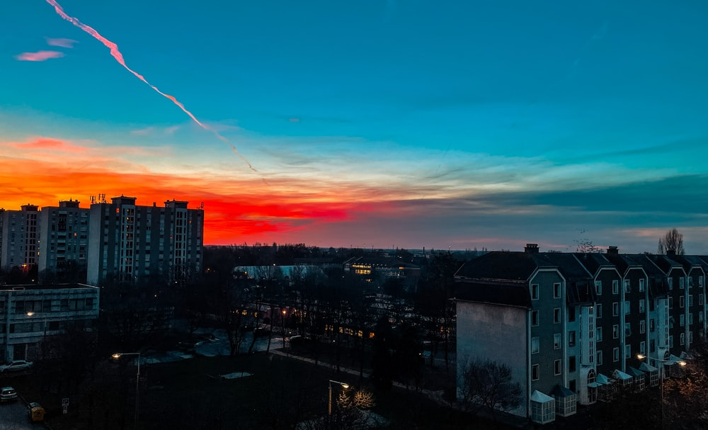 city skyline under orange and blue sky during sunset