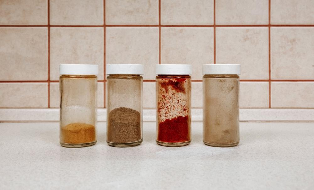 three clear glass jars with brown powder inside