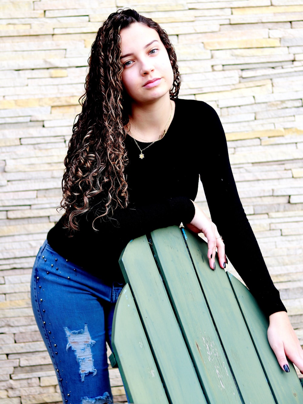 woman in black long sleeve shirt and blue denim jeans sitting on green wooden bench