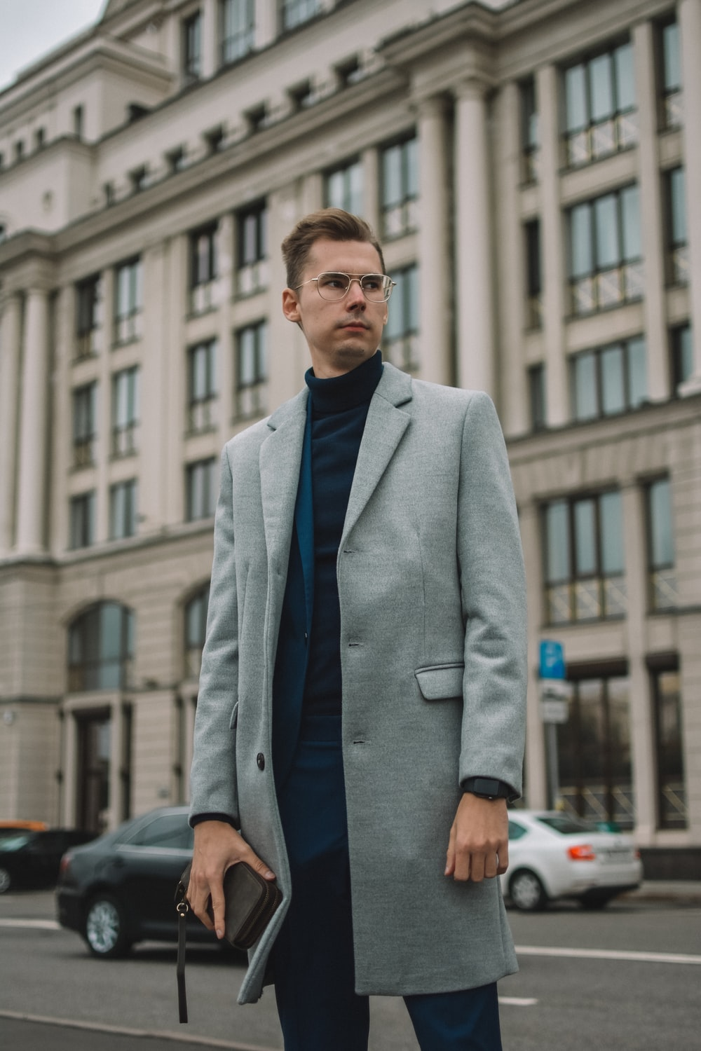 man in gray suit jacket standing near cars during daytime