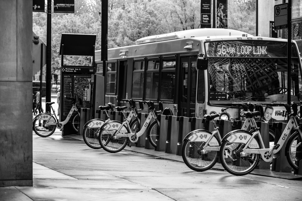 grayscale photo of city bikes parked beside building