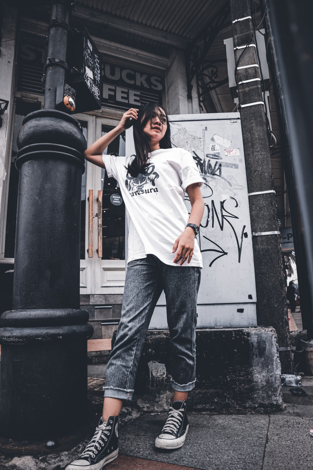 man in white crew neck t-shirt and blue denim jeans standing beside black steel post