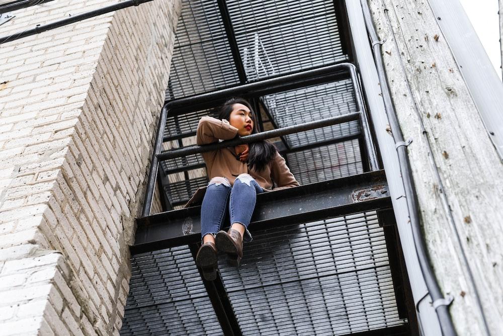 woman in blue denim jacket and blue denim jeans sitting on black metal window frame during