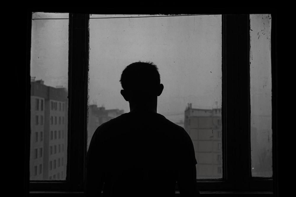 silhouette of man standing near window, sadness, tired, burn out