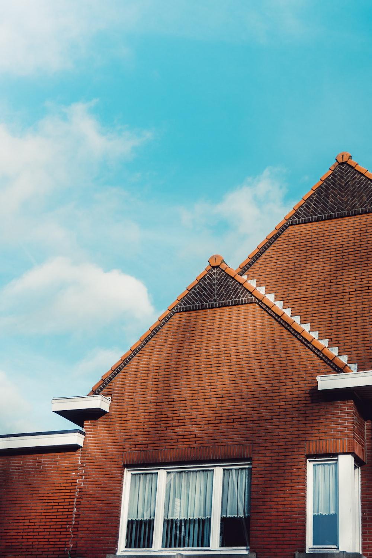 brown brick house under blue sky during daytime