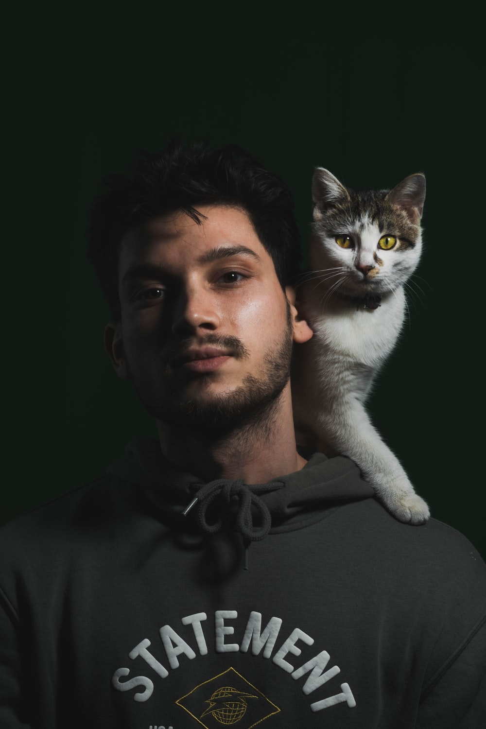 man in black crew neck shirt holding white and gray cat