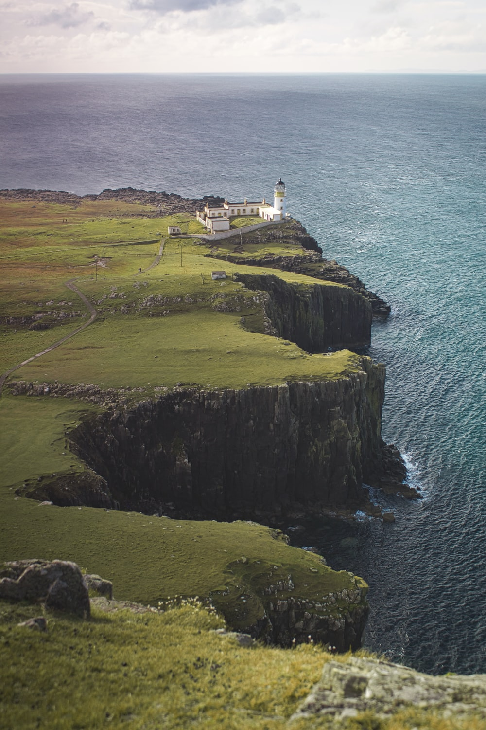 white and brown lighthouse on green grass covered hill by the sea during daytime