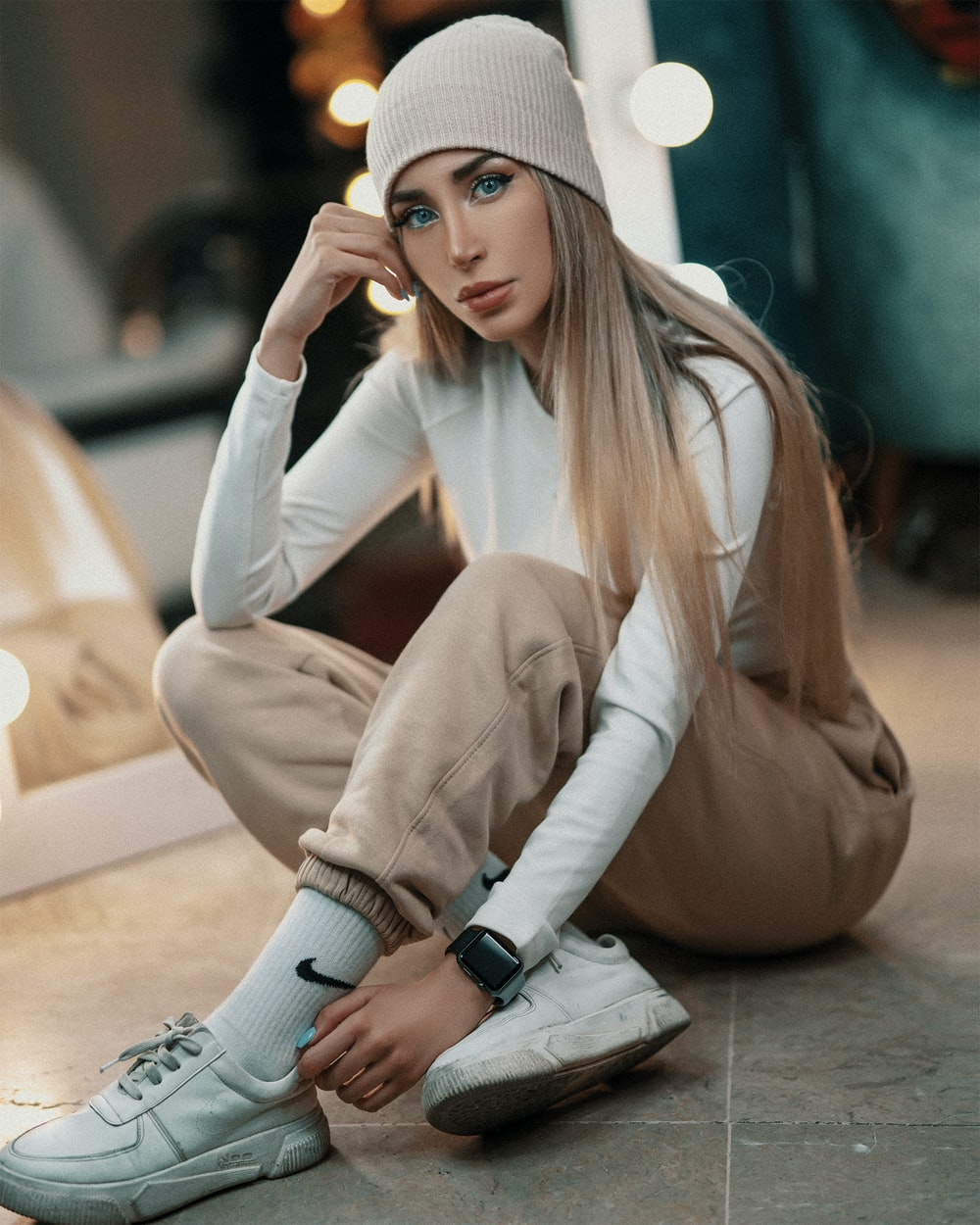 woman in white long sleeve shirt and white knit cap sitting on floor