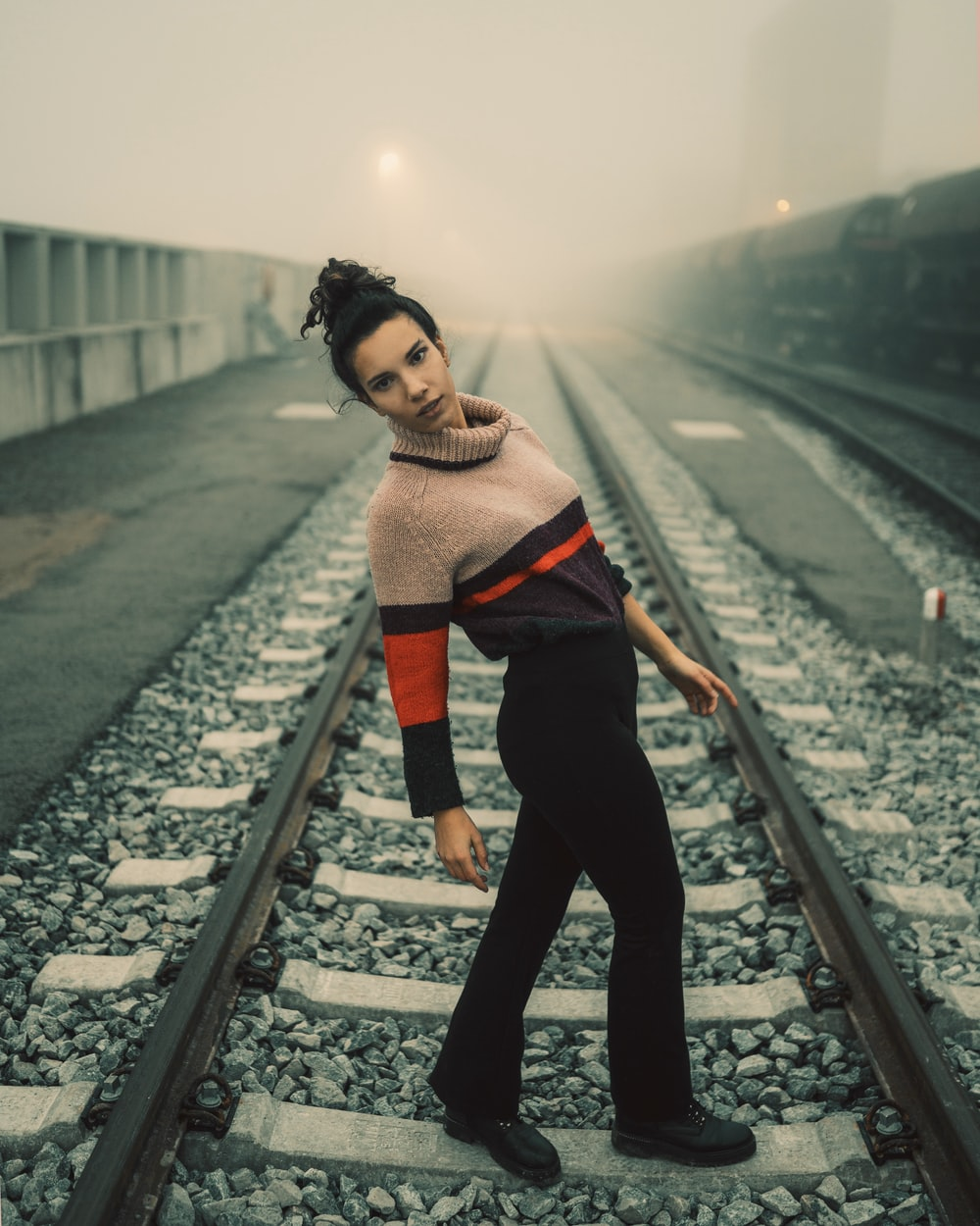 woman in black pants standing on train rail during daytime