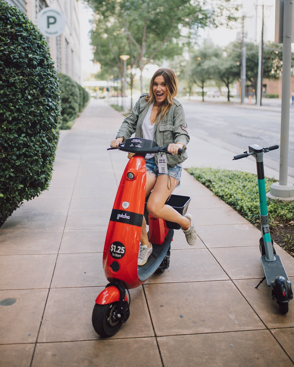 woman in gray jacket riding red and black motor scooter