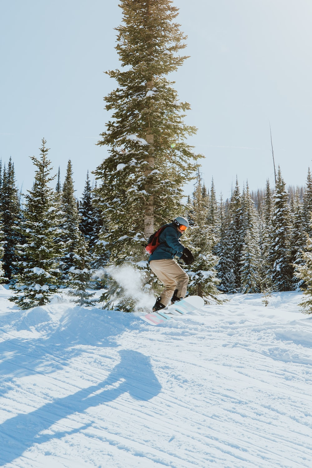 man in black jacket and brown pants riding on snowboard on snow covered ground during daytime
