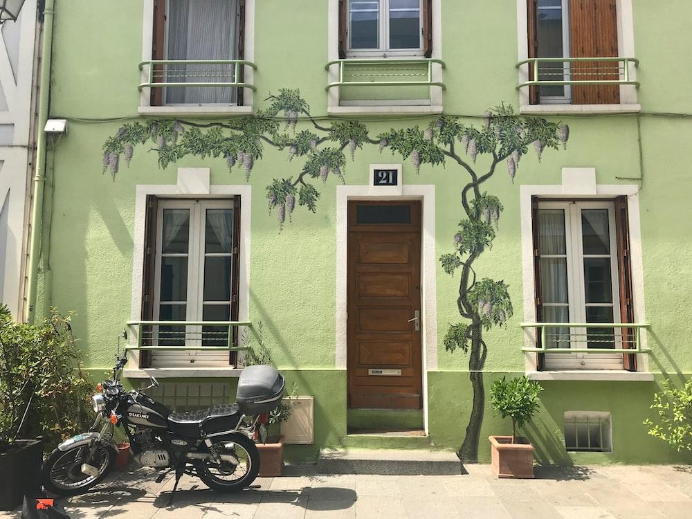 black motorcycle parked beside brown wooden door