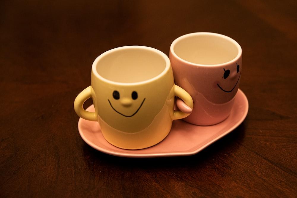 white and red ceramic mugs on white ceramic plate