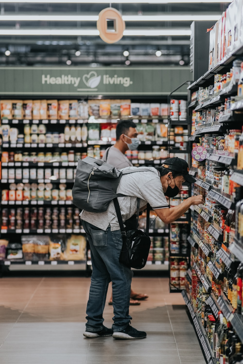 man in gray polo shirt and blue denim jeans standing on grocery store
