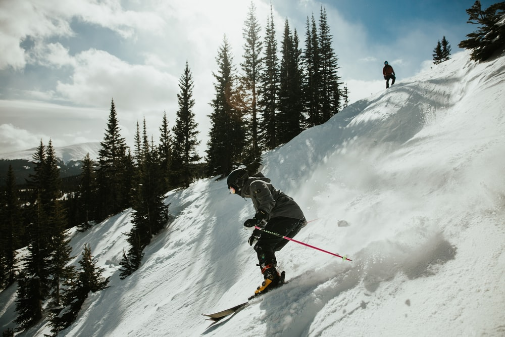 man in black jacket and blue pants riding ski blades on snow covered mountain during daytime