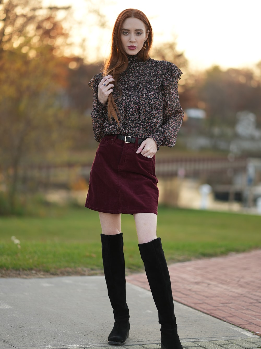 woman in black and white long sleeve shirt and red skirt standing on road during daytime