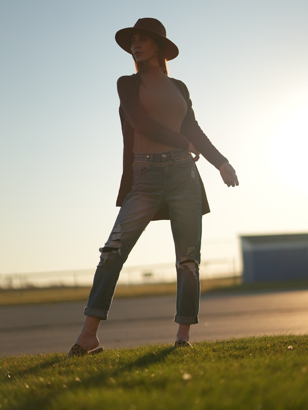 woman in brown tank top and gray pants standing on green grass field during daytime