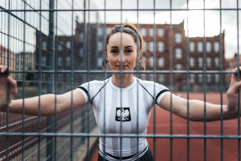 woman in white and black adidas crew neck t-shirt standing beside black metal fence during