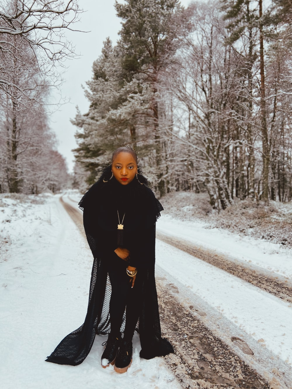 woman in black coat standing on road covered with snow during daytime