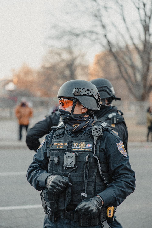 man in black police uniform wearing helmet standing on road during daytime