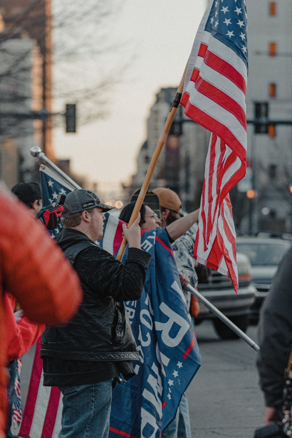 man in blue jacket holding flag of us a during daytime