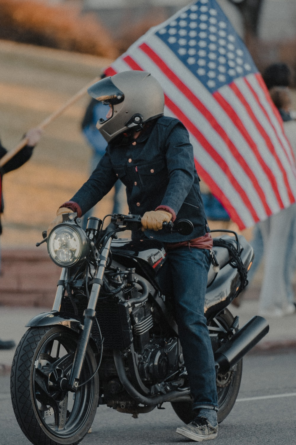 man in black jacket riding black motorcycle with us flag on his back