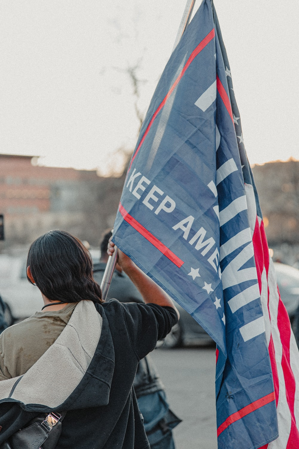 woman in brown jacket holding us a flag during daytime