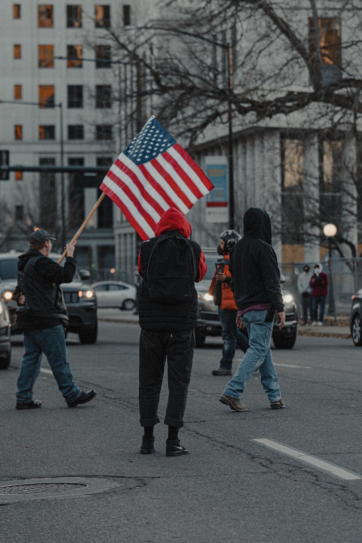 people walking on pedestrian lane holding us a flag during daytime