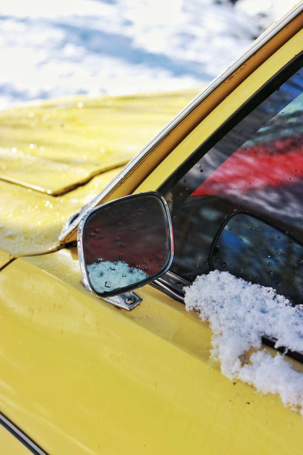 yellow car with snow on side mirror