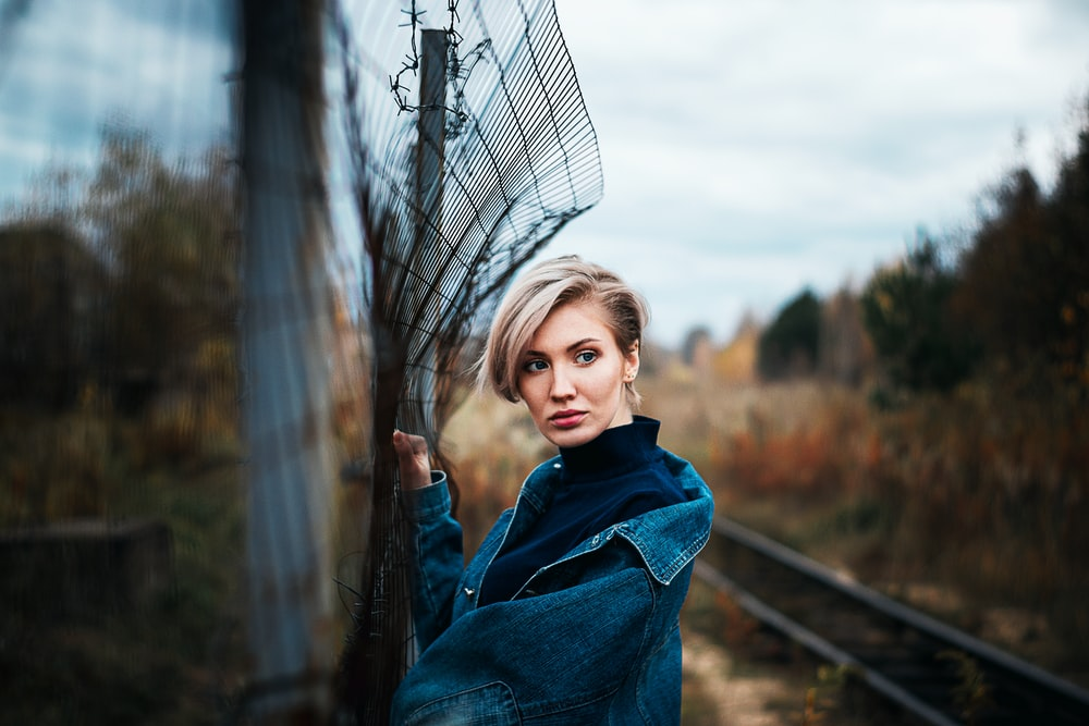 girl in blue denim jacket standing on train rail during daytime