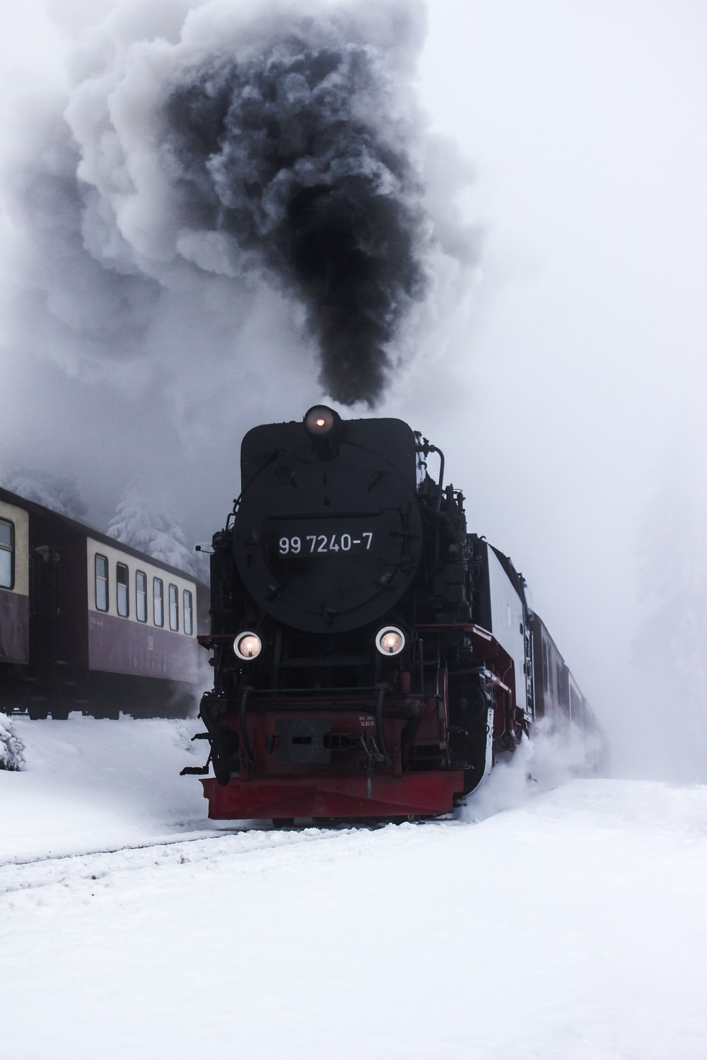 black and red train on snow covered ground during daytime