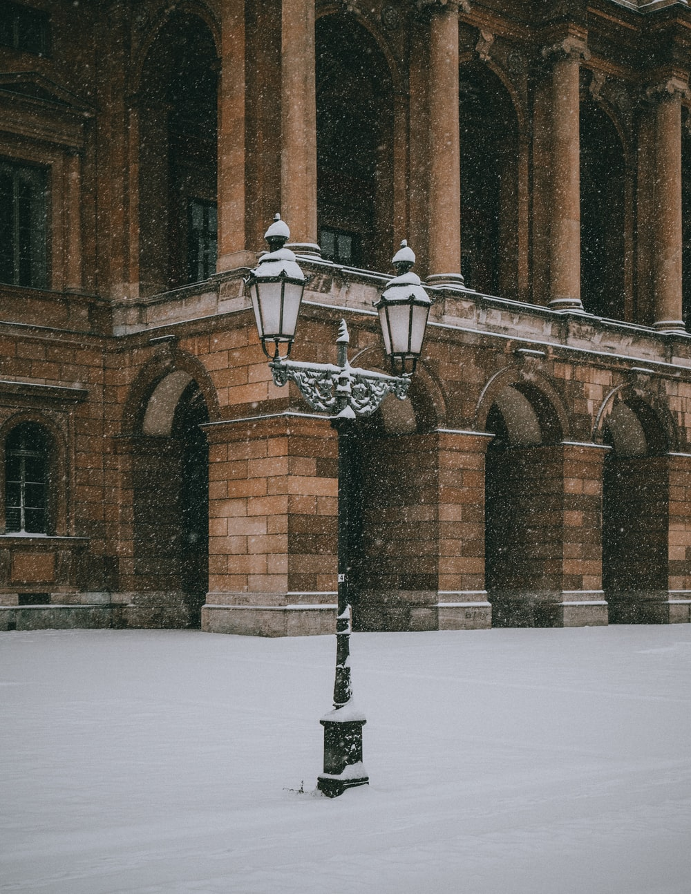 black and white lamp post on snow covered ground