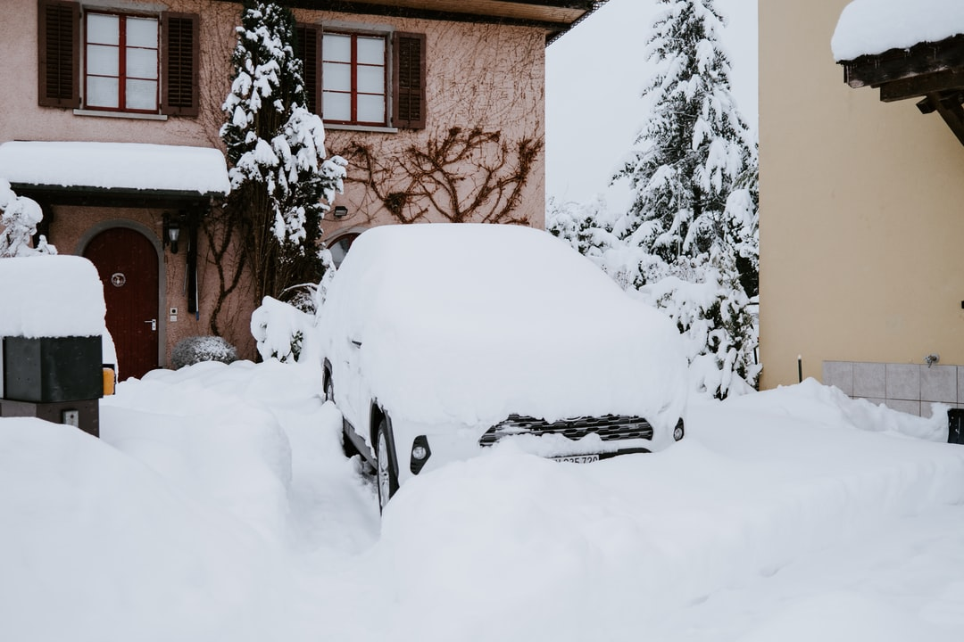 white car covered with snow near brown concrete building during daytime