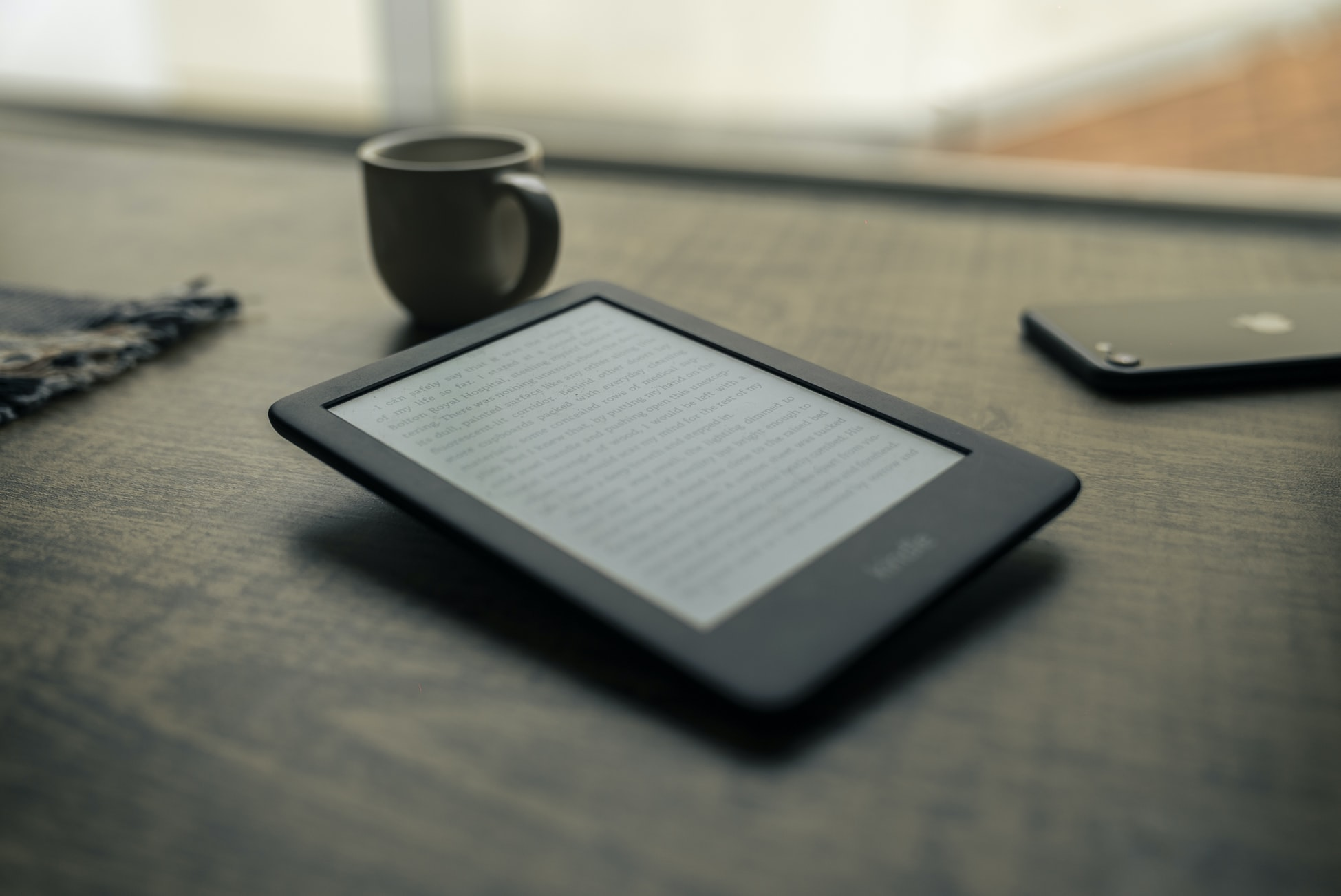Black kindle next to iPhone