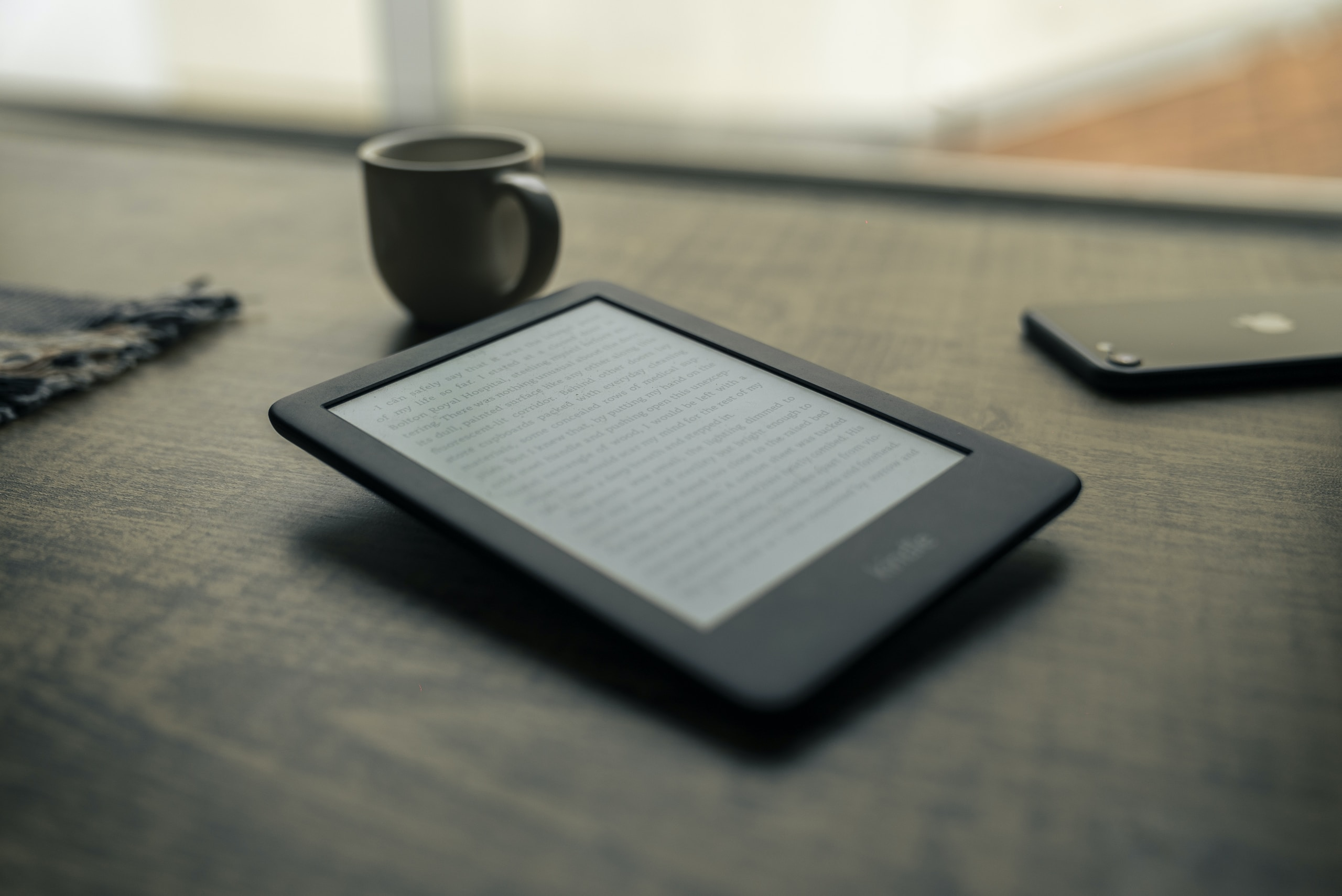 black android smartphone beside black ceramic mug on brown wooden table
