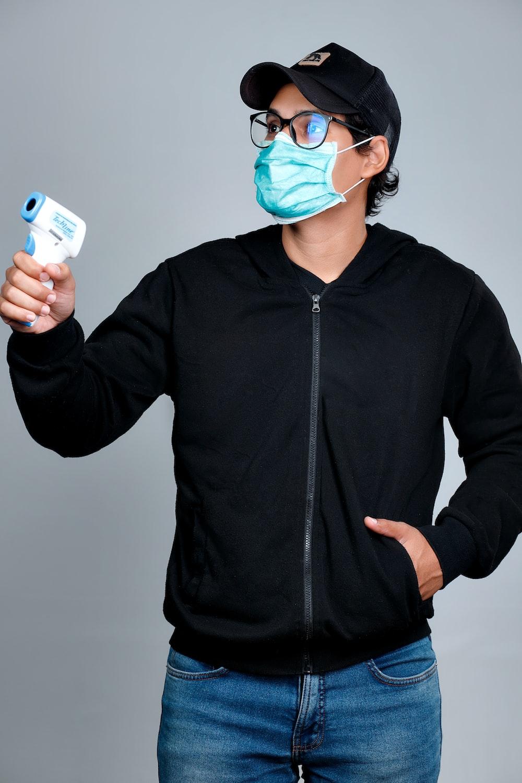 man in black zip up jacket wearing blue goggles