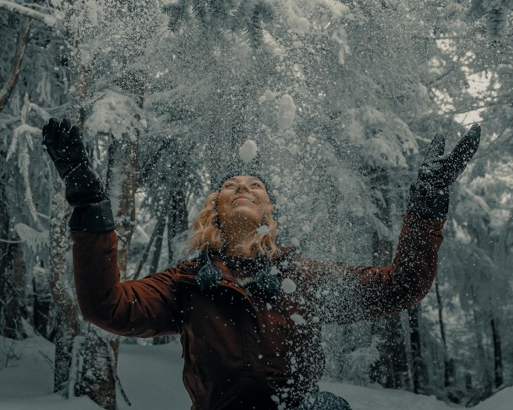 woman in black jacket blowing snow