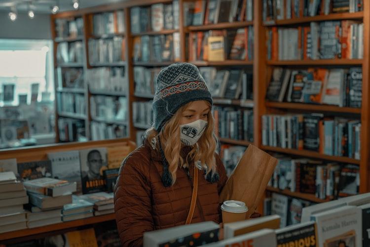 woman wearing mask browsing a bookshop