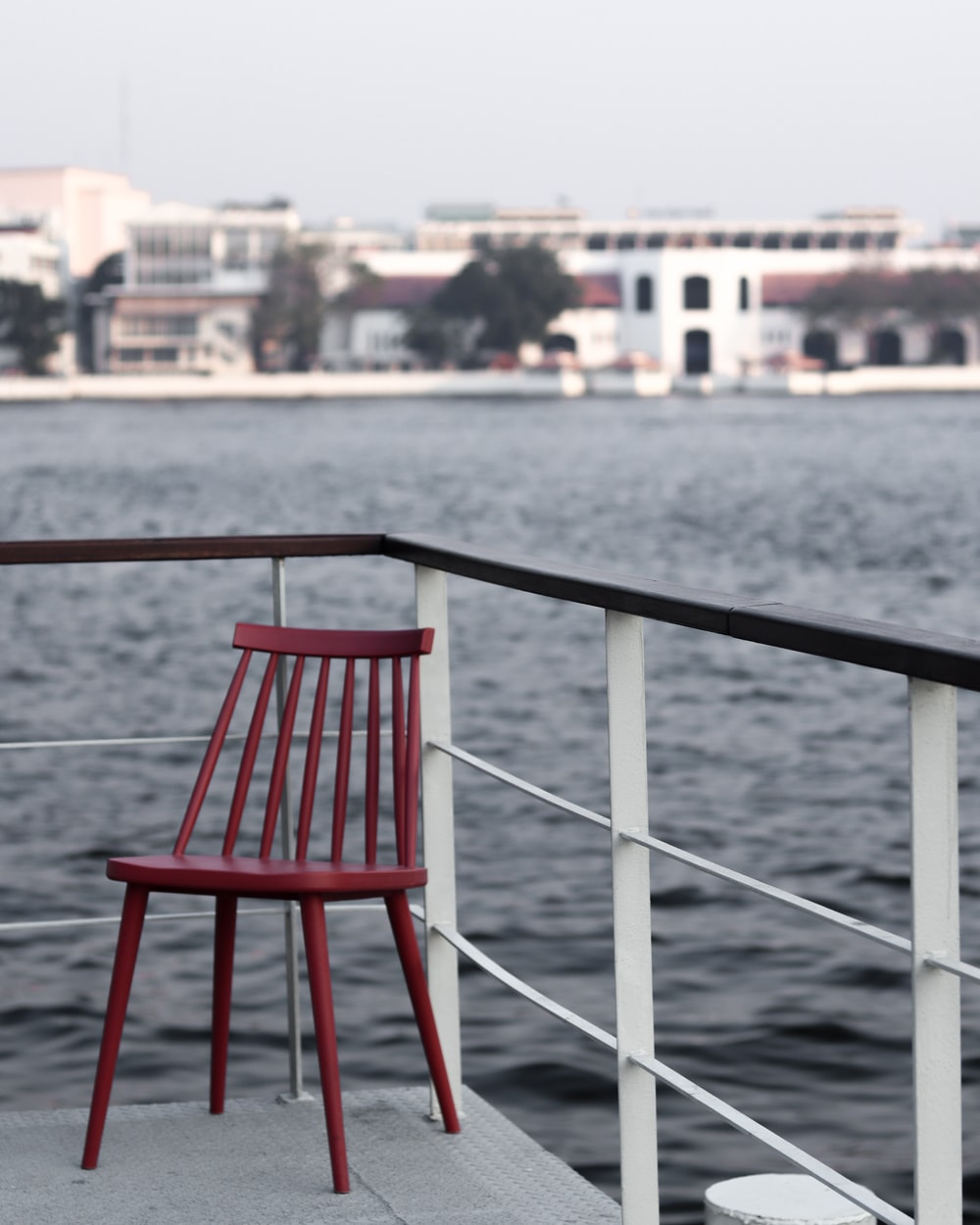 red and white metal chair near body of water during daytime