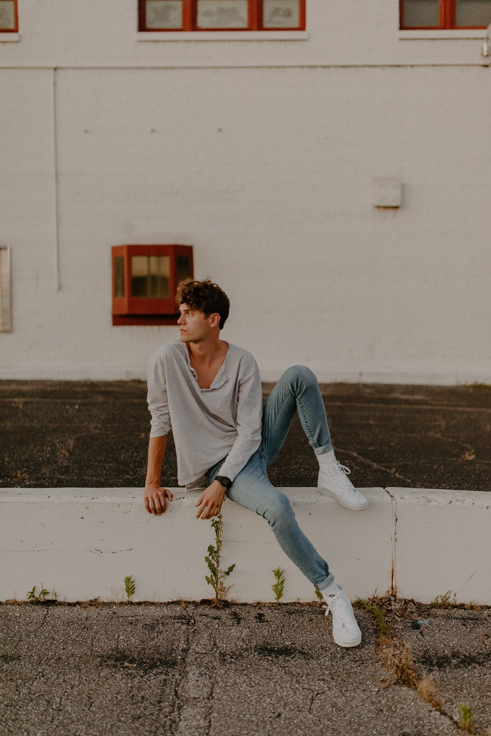 man in white crew neck t-shirt and blue denim jeans sitting on white concrete wall