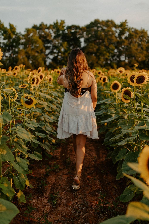 girl in white dress standing on sunflower field during daytime