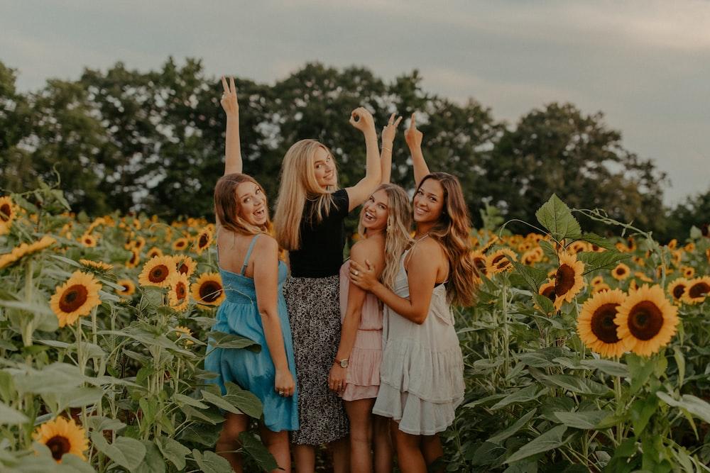 2 women standing on sunflower field during daytime