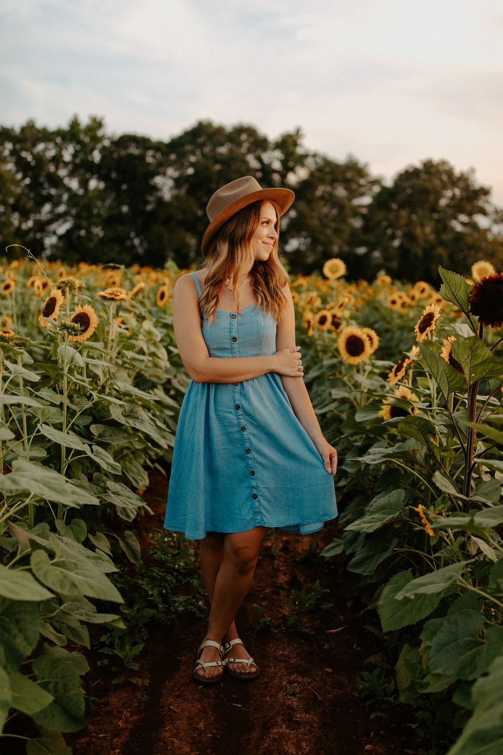 woman in blue dress standing on green grass field during daytime