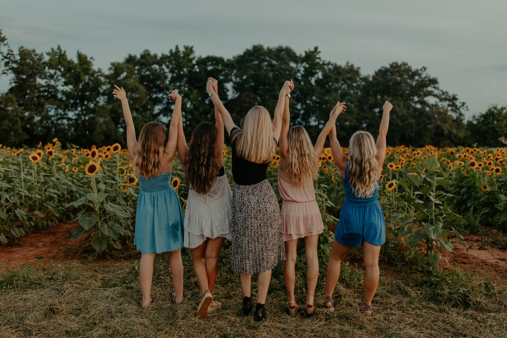 group of girls standing on sunflower field during daytime