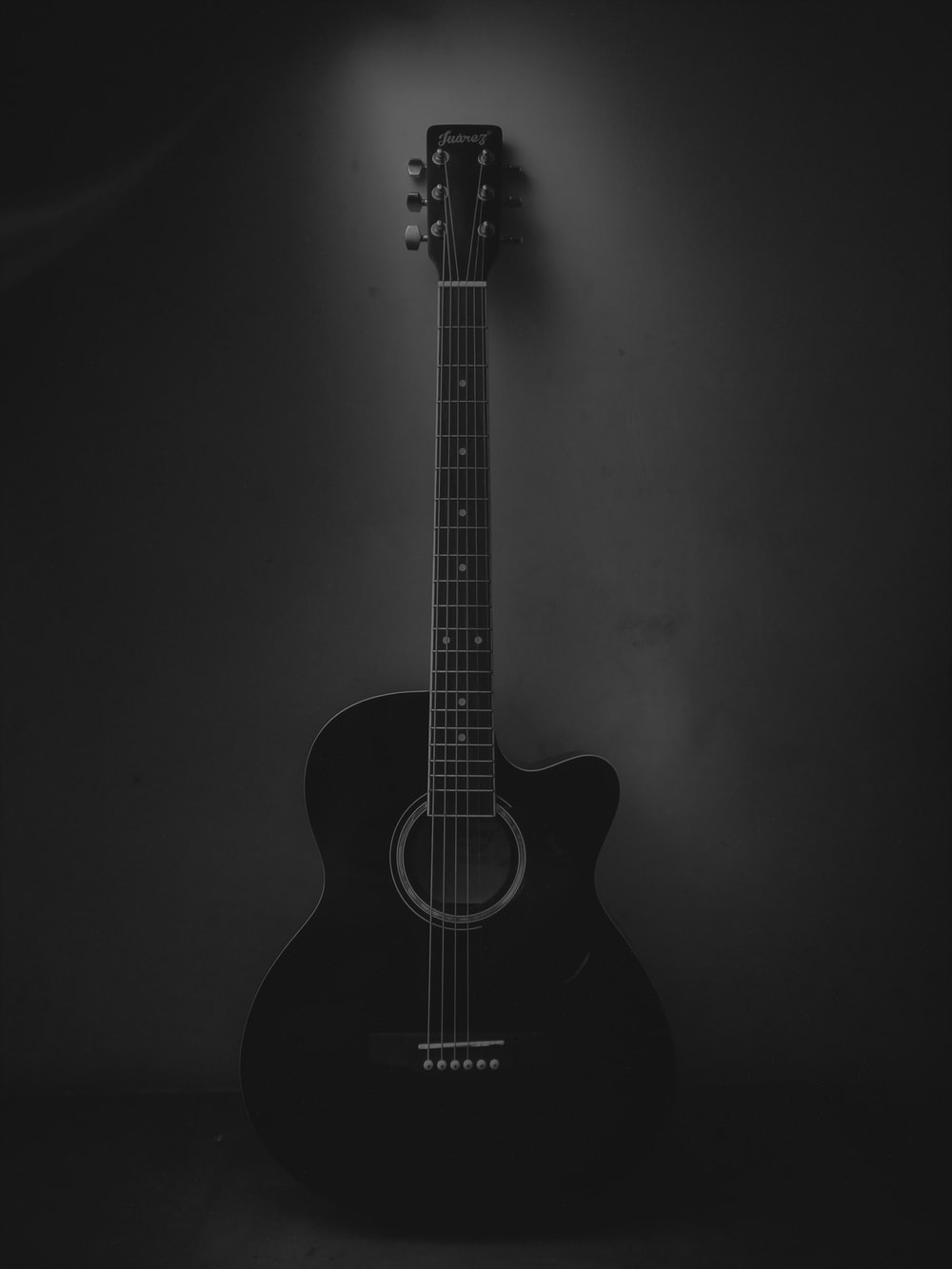 black acoustic guitar on black background