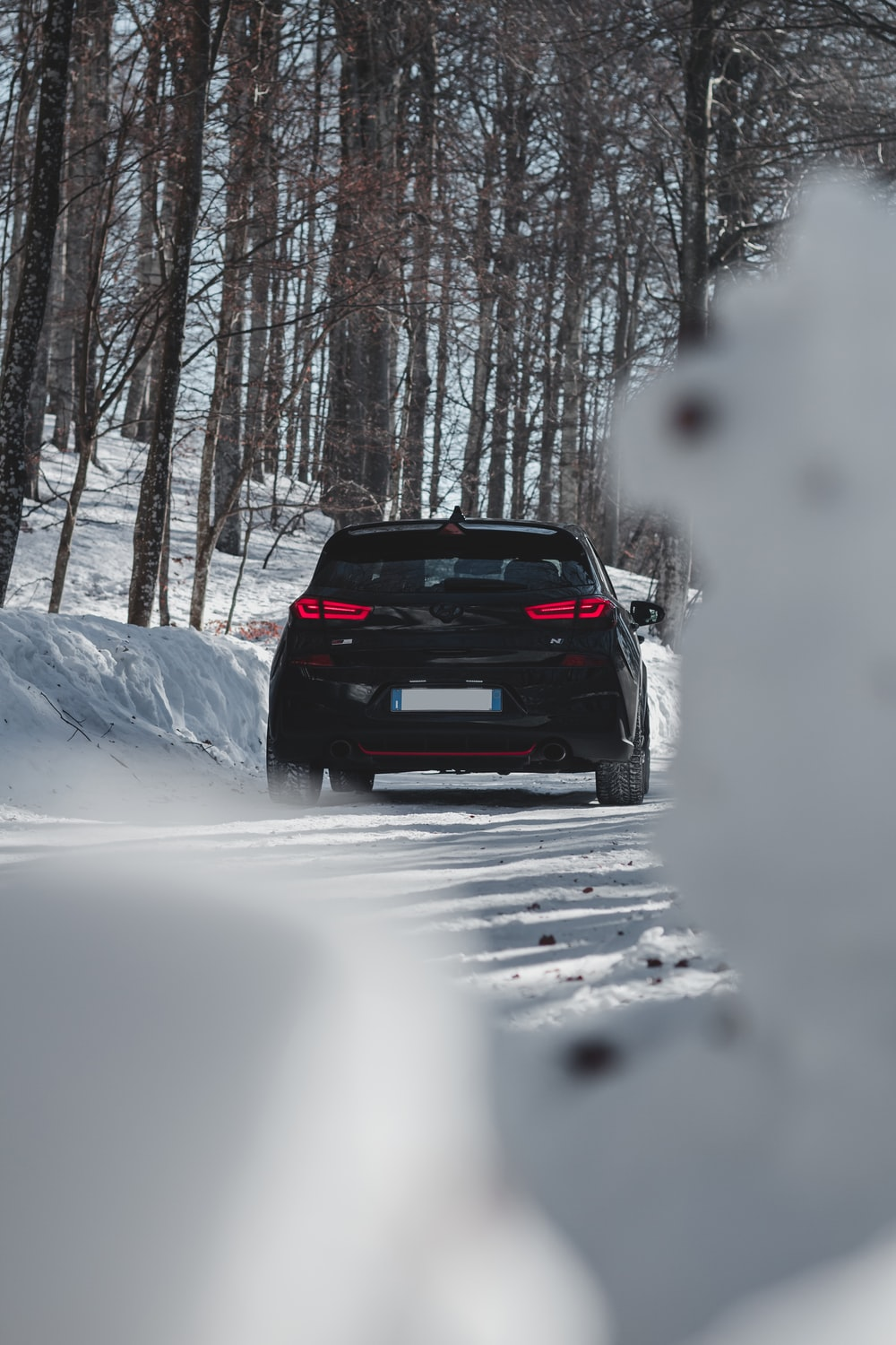 black car on snow covered road during daytime