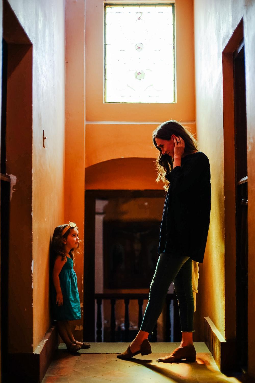 woman in black long sleeve shirt and black pants standing beside brown wooden door